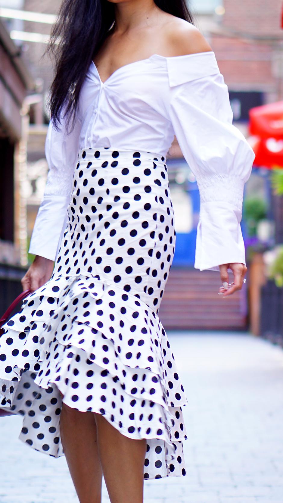 Polka Dot Ruffle Skirt & Statement Sleeve - Street Style Outfit Ideas #streetstyle #outfitinspo #outfitideas #frenchdesigner #frenchstyle #paris #pfw #ruffleskirt #highlowskirt #outfitinspiration #fashionblogger #fashionblog #streetfashion #citystyle #summerstyle #fallstyle #fallwinter #miumiu #prada #jacquemus #asianblogger #canadianblogger #usblogger #topbloggers #topfashionbloggers #polkadotskirt #redbag #offtheshoulder #whiteshirt
